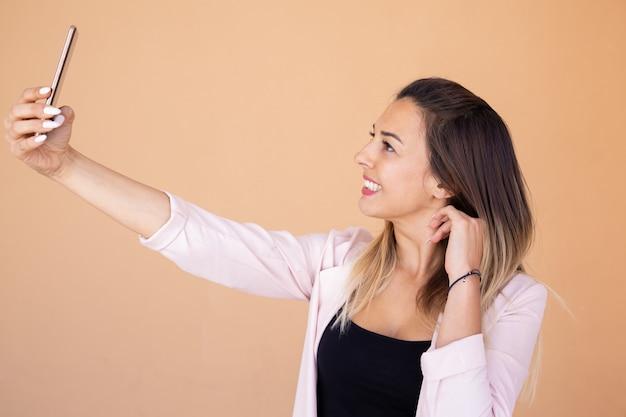 Mooie glimlachende vrouw die selfie met smartphone nemen