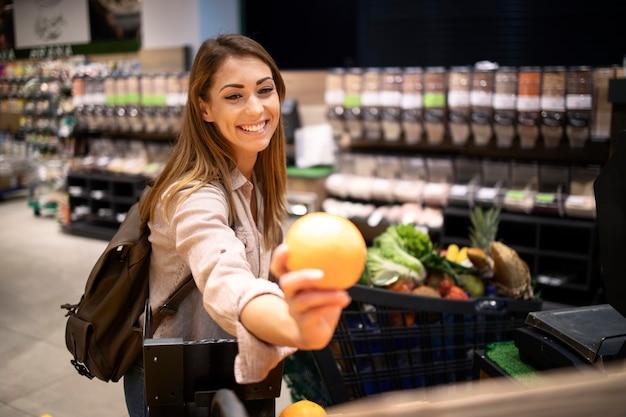 Mooie glimlachende vrouw die sinaasappelen in supermarkt bij fruitafdeling koopt