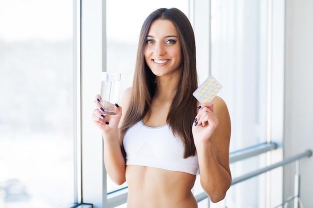 Mooie glimlachende vrouw die vitaminepil neemt