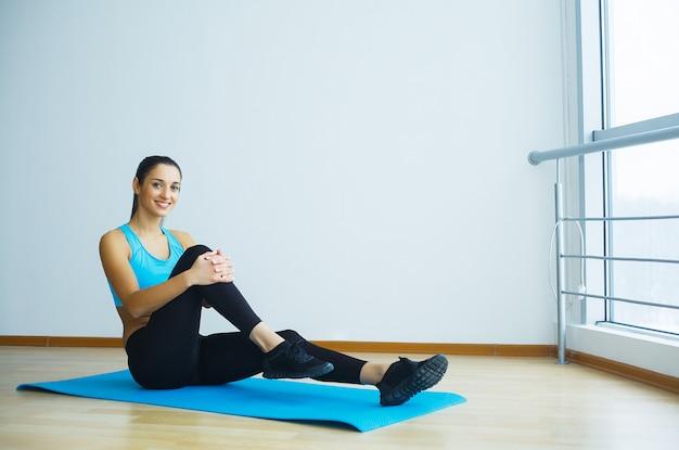 Mooie glimlachende vrouw die yoga binnen in gymnastiek doet