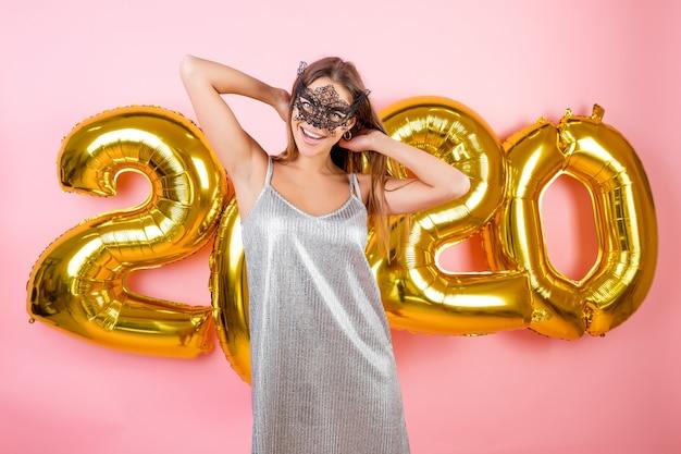 Mooie glimlachende vrouw die zwart masker voor gouden nieuwe die het jaarballons van 2020 draagt over roze worden geïsoleerd