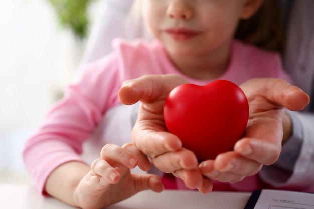 Mooie glimlachende vrouw en kind houden rode speelgoed