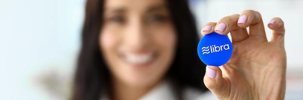 Mooie glimlachende vrouw houdt blauwe weegschaal