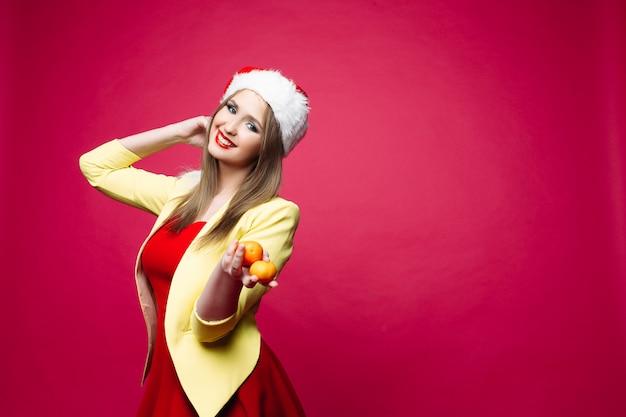 Mooie glimlachende vrouw in feestelijke jurk en kerstmuts met mandarijnen.