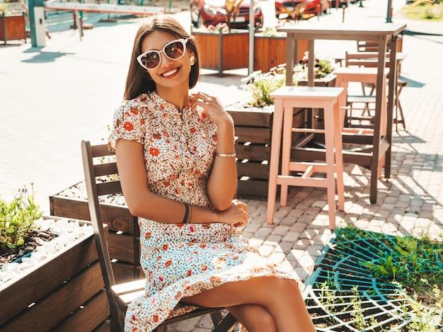 Mooie glimlachende vrouw in trendy zomer sundress zitten in een cafe