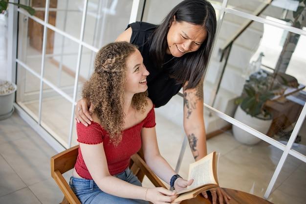 Mooie glimlachende vrouw lezen boek samen lezen boek vrouwen vriendschap en onderwijs concept
