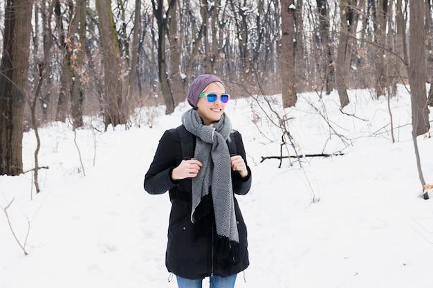 Mooie glimlachende vrouw met de warme rugzak die van de kledingsholding zich in sneeuwlandschap tijdens de winter bevindt