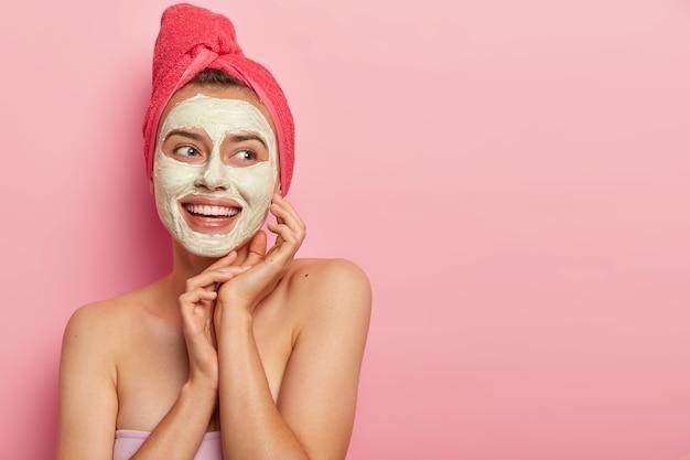 Mooie glimlachende vrouw met kleimasker, maakt schoonheidsstapje, reinigt gezicht, draagt een handdoek om het hoofd, staat shirtless, krijgt plezier, vermindert puistjes, kopieer ruimte tegen roze muur