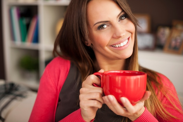 Mooie glimlachende vrouw met kop koffie