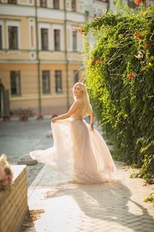 Mooie glimlachende vrouw met lang blond haar in elegante vliegende lichte kleding die langs de straat loopt