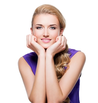 Mooie glimlachende vrouw met lang blond krullend haar en hand dichtbij gezicht - dat op witte muur wordt geïsoleerd.