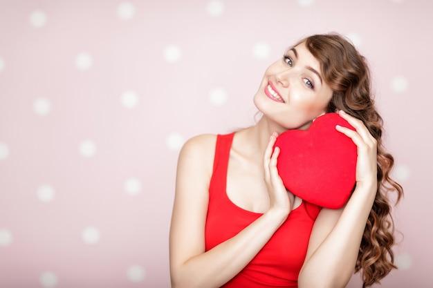 Mooie glimlachende vrouw met rode harten voor st valentijnsdag
