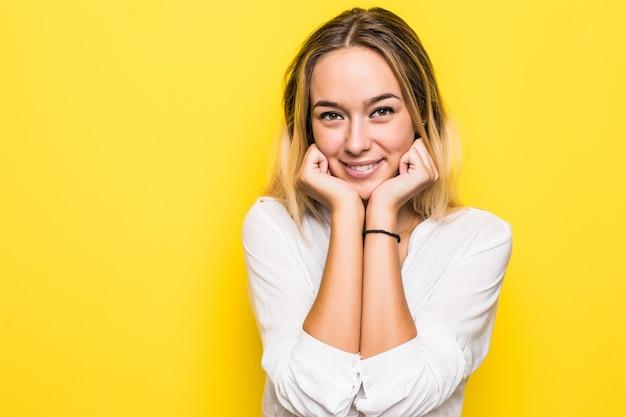 Mooie glimlachende vrouw met schone huid en witte tanden die zich voordeed op gele muur