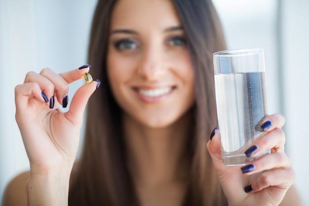 Mooie glimlachende vrouw nemen vitamine pil en voedingssupplement