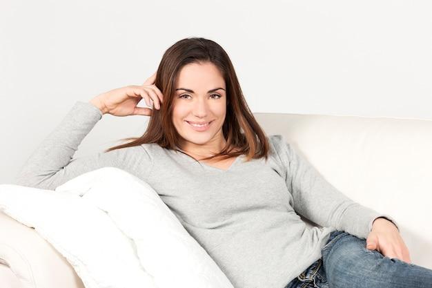 Mooie glimlachende vrouw op bank thuis