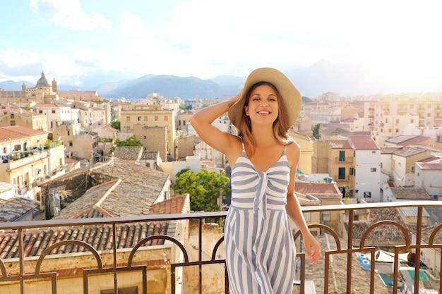 Mooie glimlachende vrouw op terras in palermo met stadsgezicht op de achtergrond, sicilië, italië