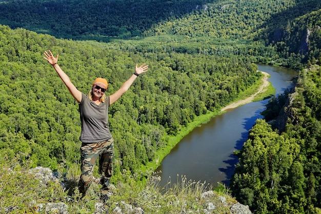 Mooie glimlachende vrouw verheugt zich in het veroveren van berg.