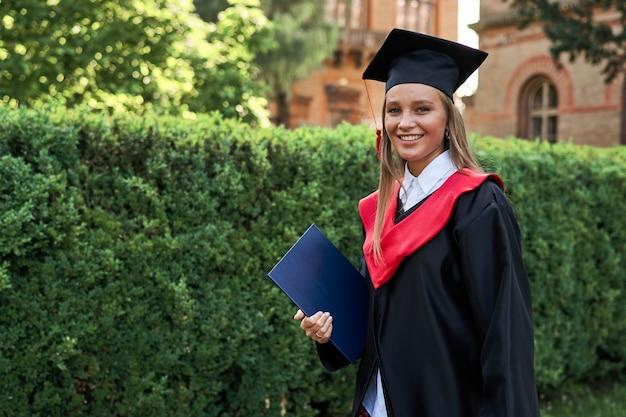 Mooie glimlachende vrouwelijke afgestudeerde in afstudeergewaad op de universiteitscampus