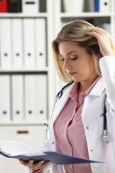 Mooie glimlachende vrouwelijke arts houdt klembord vast