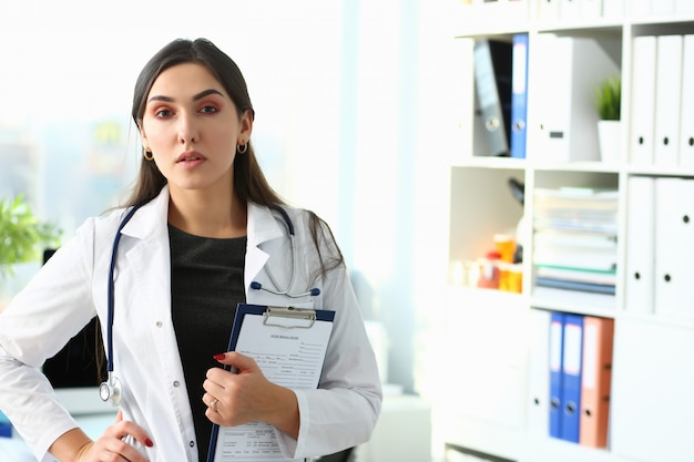 Mooie glimlachende vrouwelijke arts op de werkplek
