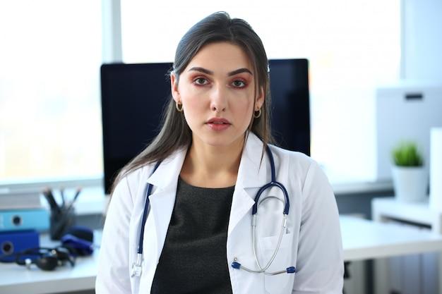 Mooie glimlachende vrouwelijke arts op werkplek portret