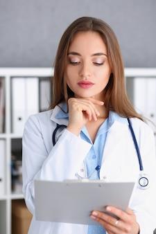 Mooie glimlachende vrouwelijke arts staan in kantoor
