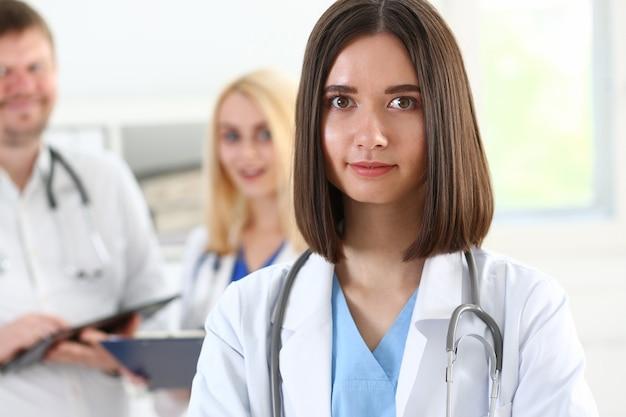 Mooie glimlachende vrouwelijke arts staat in kantoorportret