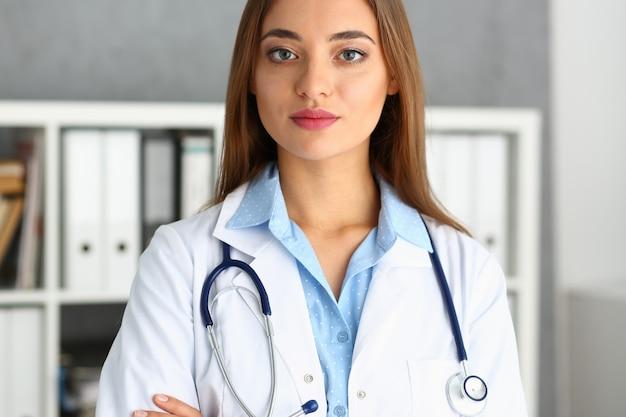 Mooie glimlachende vrouwelijke arts zit op de werkplek