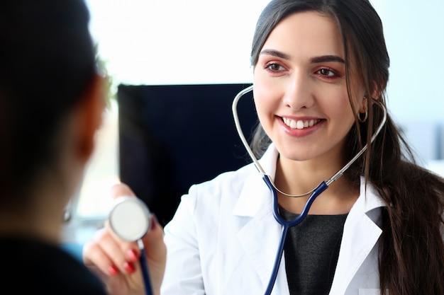 Mooie glimlachende vrouwelijke artsengreep in wapen