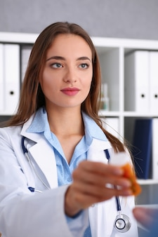 Mooie glimlachende vrouwelijke artsengreep in wapens