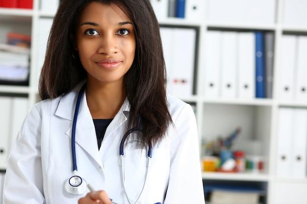 Mooie glimlachende vrouwelijke artsengreep