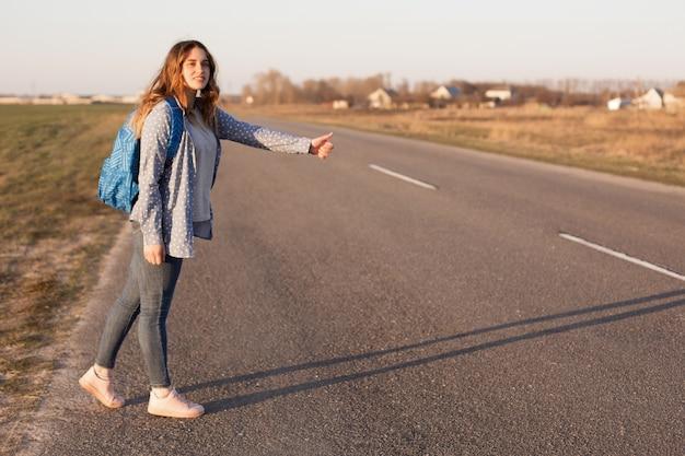 Mooie glimlachende vrouwelijke reiziger staat op de weg, liften en stopt auto's, draagtas, geniet van een vrije levensstijl