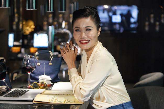 Mooie glimlachende vrouwelijke restaurantmanager die aan een nieuw menu werkt, ze zit aan de toog en werkt op een laptop