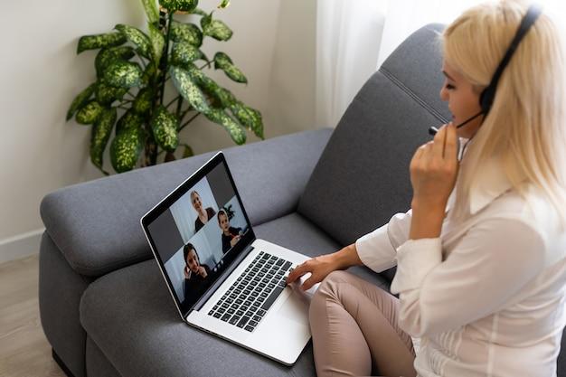 Mooie glimlachende vrouwelijke student die online onderwijsdienst gebruikt. jonge vrouw die op een laptopscherm kijkt, kijkt naar de cursus en luistert ernaar met een koptelefoon. modern studietechnologieconcept