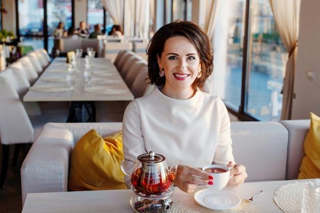 Mooie glimlachende vrouwen die thee drinken bij gezellig koffie. ondernemers nemen een pauze met een theekopje. lichte lifestyle foto in een stijlvol café.