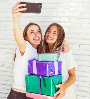 Mooie glimlachende vrouwen met verjaardagsgift voor bakstenen muur