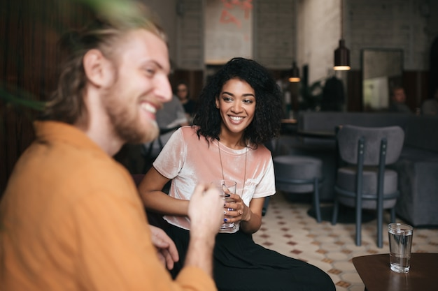 Mooie glimlachende vrouwenzitting in restaurant met vriend