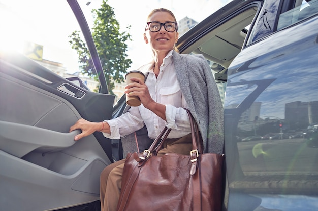Mooie glimlachende zakenvrouw van middelbare leeftijd met handtas met kopje koffie om mee te nemen terwijl