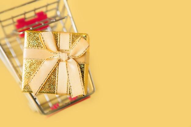 Mooie gouden doos met een strik in een winkelwagen