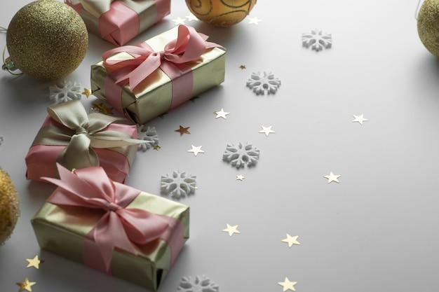 Mooie gouden geschenken gloden kerstballen op wit. kerstmis, feest, verjaardag achtergrond. vier glanzende verrassingsdozen copyspace. creatieve plat lag bovenaanzicht.