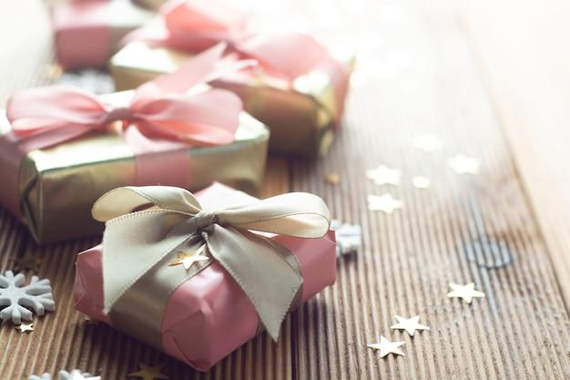 Mooie gouden geschenken kerstmis, feest, verjaardag. vier de glanzende houten achtergrond van verrassingsdozen copyspace