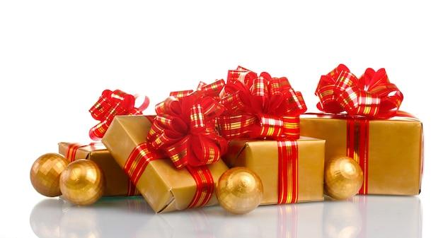 Mooie gouden geschenken met rood lint en kerstballen geïsoleerd op wit