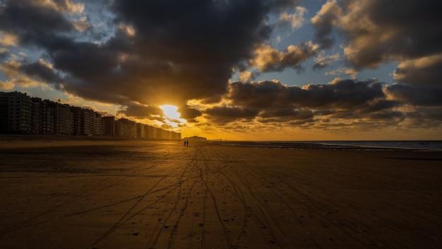 Mooie gouden zonsondergang op het strand met een bewolkte hemel