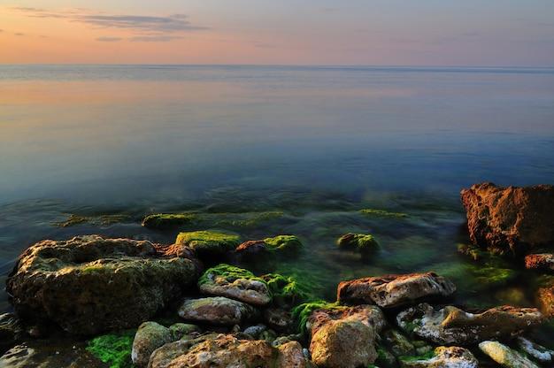Mooie gouden zonsondergang over de rotsachtige kustlijn van de zwarte zee in de krim