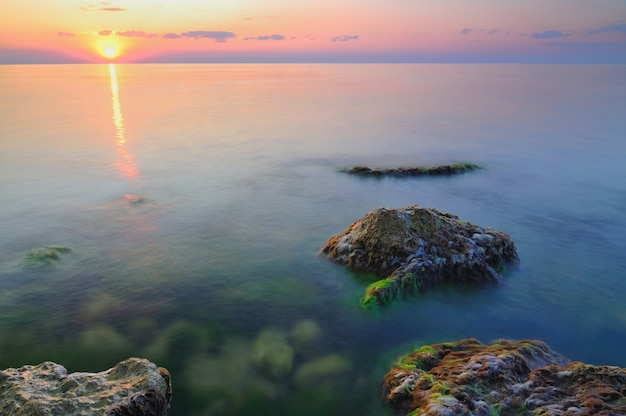 Mooie gouden zonsondergang over de rotsachtige kustlijn van de zwarte zee op de krim op zomerdag