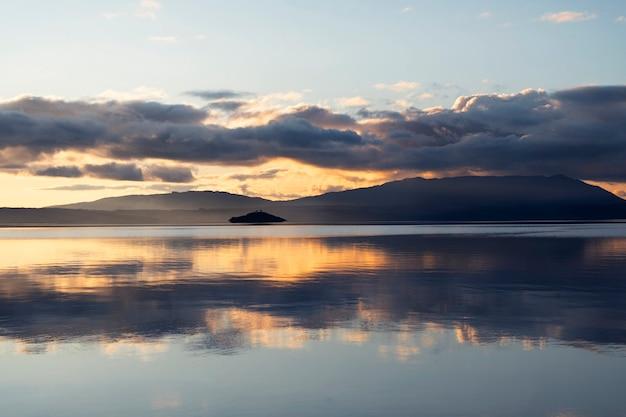 Mooie goudoranje zonsondergang over het meer waar de lucht en de wolken als een spiegel reflecteren