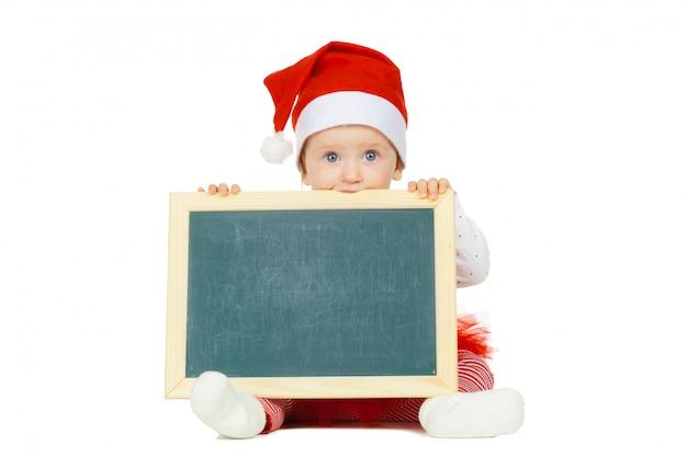 Mooie grappige baby in een kerstmishoed die op wit wordt geïsoleerd