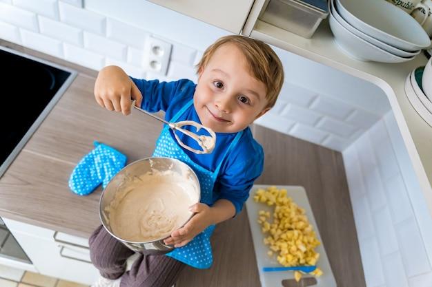 Mooie grappige kleine peuterjongen die de binnenlandse appeltaart van het keukenschort dragen