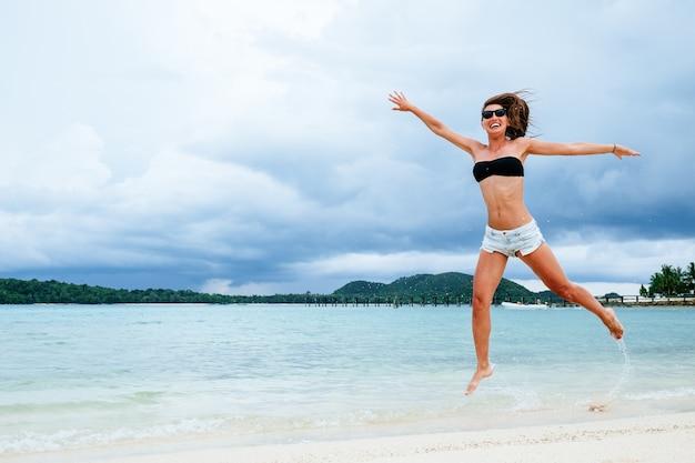 Mooie grappige vrouw die een zwempak en jeansborrels draagt die op het strand spelen