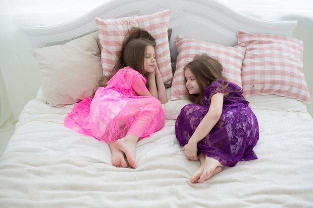 Mooie grils in roze en paarse jurken slapen in bed